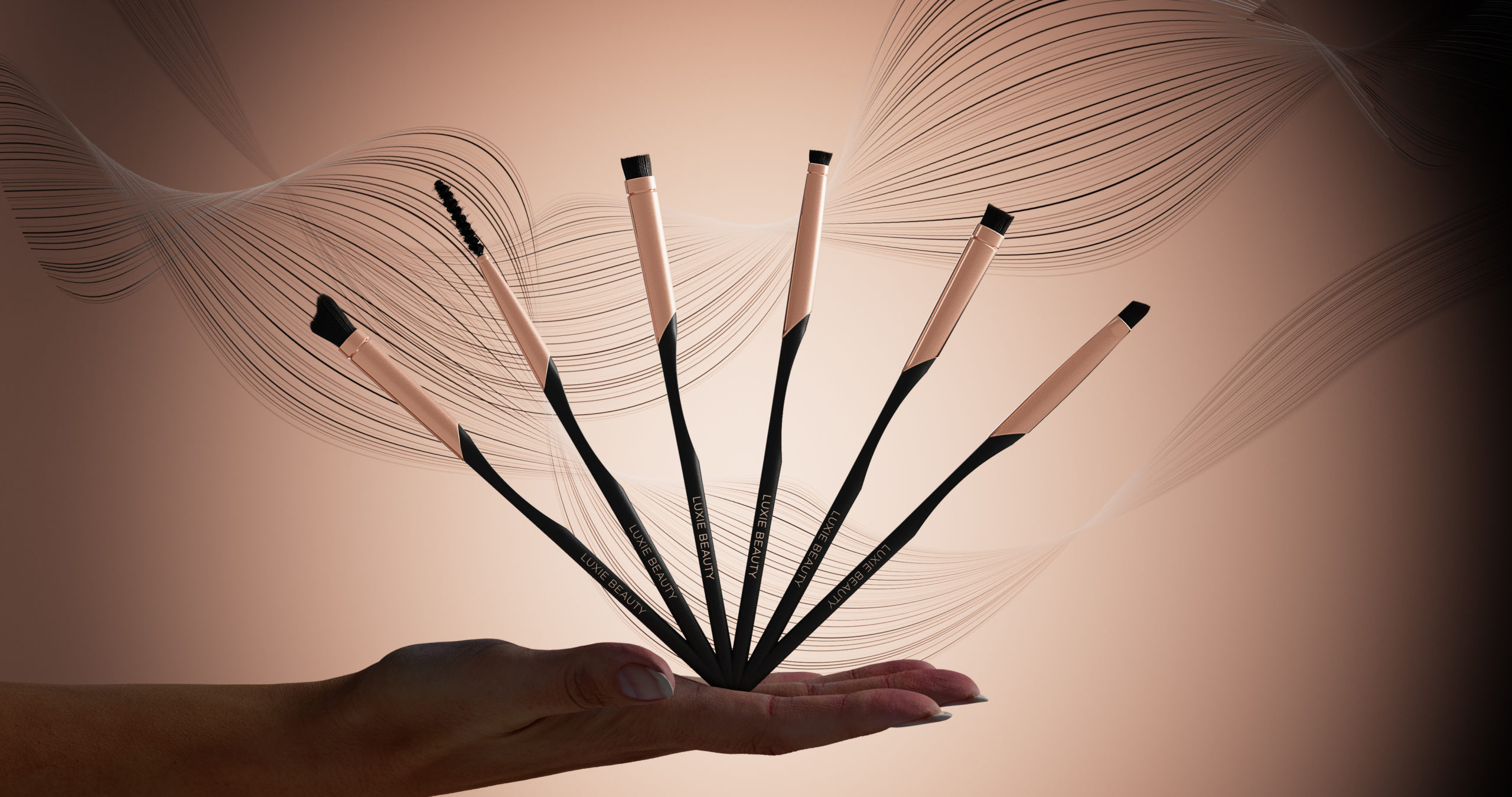 Wenbo Zhao-Luxary Makeup Brushes-Luxie Beauty-Hand holding burshes and floating lines in background