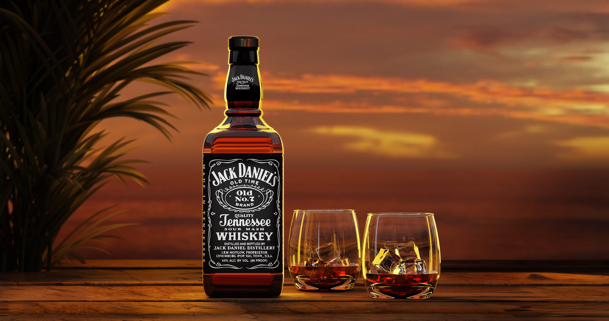 Jack Deniel bottle and two glasses of whisky on a wood table top with sunset in the background